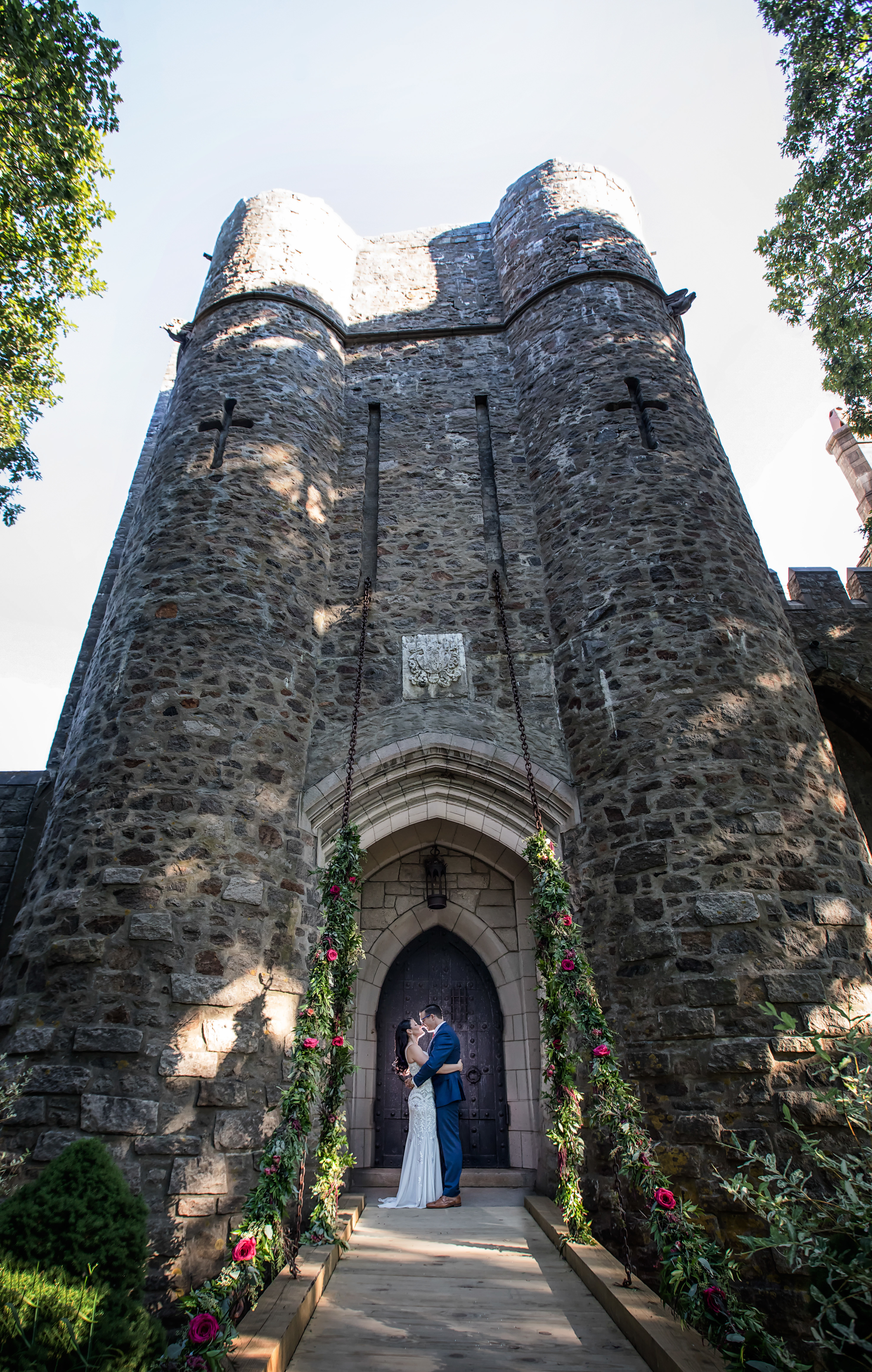 Bride and Groom photographed at Hammond Castle Museum. Wedding flower garlands go up the chains of the drawbridge. Dark and moody wedding photos. Wedding Inspiration at Hammond Castle.